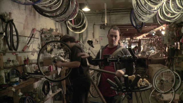 ms man coming in and attaching old bike frame to holder, screwing seat to it in bicycle workshop, brooklyn, new york city, new york state, usa - bicycle frame stock videos & royalty-free footage