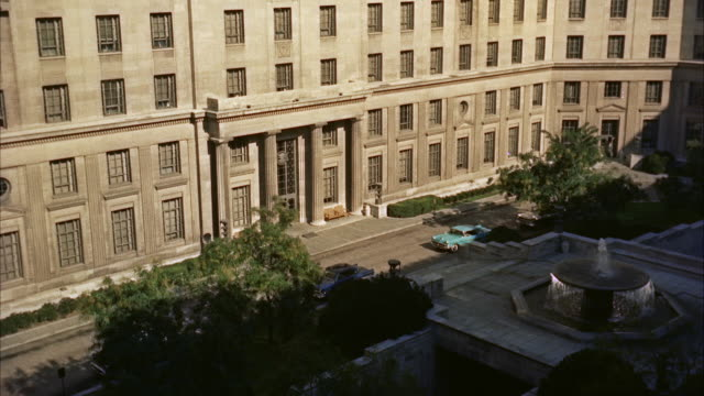 WS Man coming out from fbi building entrance and sitting in car / Wasington D.C., United States
