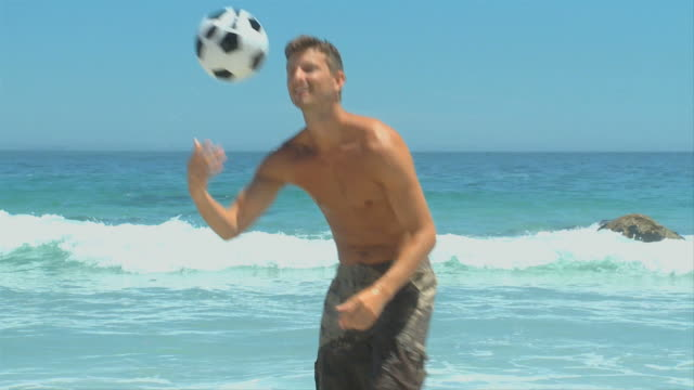 Man coming out of the sea to pick up a soccer ball / Cape Town, Western Cape, South Africa