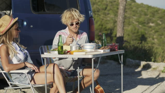 vídeos de stock e filmes b-roll de man communicating with girlfriend against van - eating