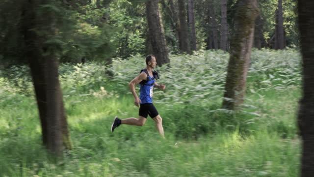 slo mo ds maratona corridore competere sul sentiero forestale - top video stock e b–roll