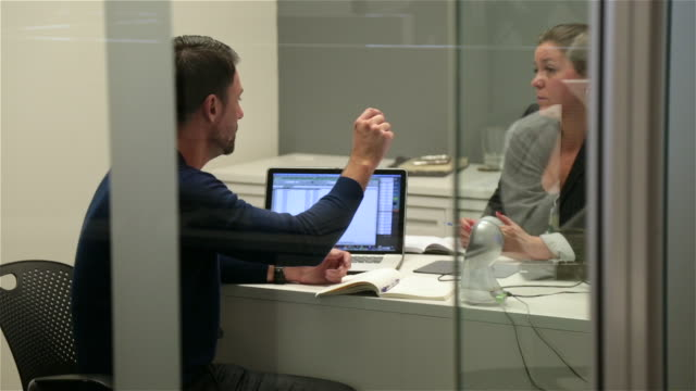 Man confers animatedly with female boss in small private corporate office (dolly shot)