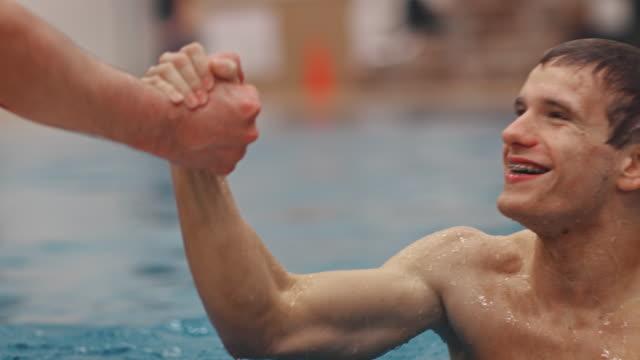vídeos de stock e filmes b-roll de man congratulating determined swimmer in pool - mergulho desporto