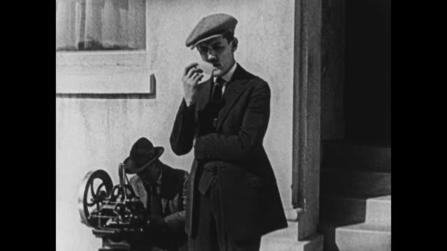 vidéos et rushes de 1924 man contemplates business card before approaching printing peddler - 1924
