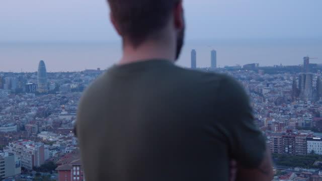 vídeos y material grabado en eventos de stock de man contemplating barcelona sunrise from bunkers lookout - un solo hombre