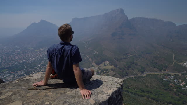 Man contemplating from top of mountain