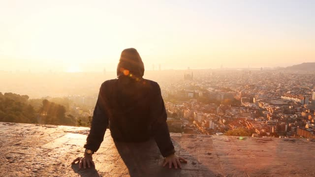 man contemplating the barcelona cityscape on sunrise - dach stock-videos und b-roll-filmmaterial