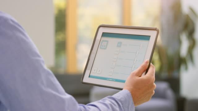 vídeos de stock, filmes e b-roll de ds homem controlando as luzes em casa com um app sobre o tablet - só um homem