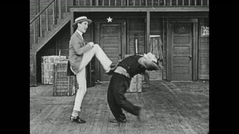 1919 man (al st john) convinces man (buster keaton) to attempt a flexible vaudeville dancer's (jack coogan sr) moves, but keaton, unsuccessful, is kicked by the dancer  / fatty arbuckle hits keaton's legs out with a broom - 1910 1919 stock videos & royalty-free footage
