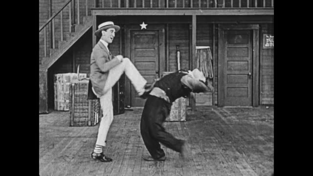 1919 man (al st john) convinces man (buster keaton) to attempt a flexible vaudeville dancer's (jack coogan sr) moves, but keaton, unsuccessful, is kicked by the dancer  / fatty arbuckle hits keaton's legs out with a broom - tripping falling stock videos and b-roll footage