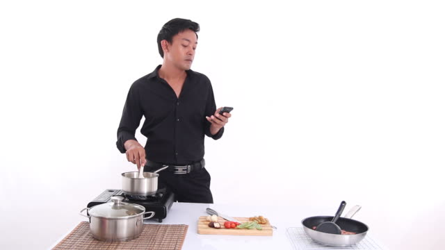 man cooking and watch cellphone in white room kitchen - foodie stock videos & royalty-free footage