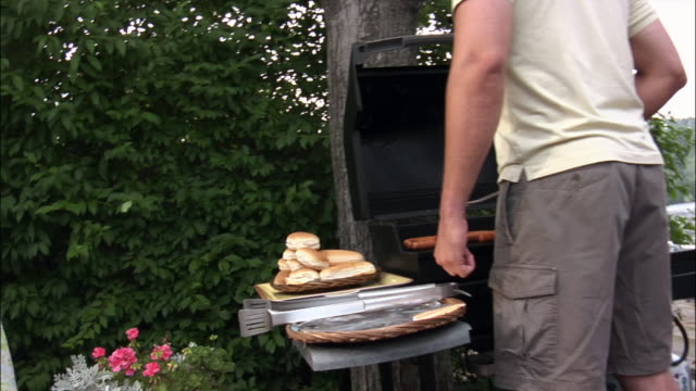 man cooking at barbecue / children come over and are kissed by woman / new jersey - bikini bottom stock videos & royalty-free footage
