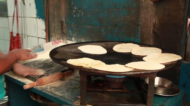 Man cooking bread (Roti or Chapatti) on the gas, Delhi, India