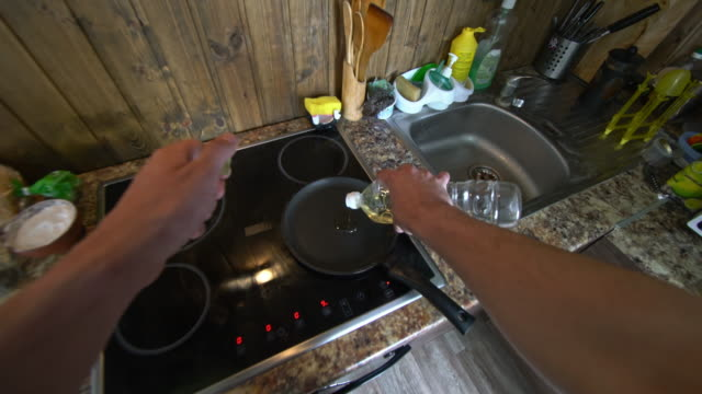POV of man cooking eggs for breakfast