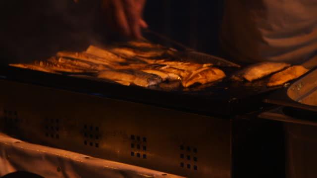 man cooking fish at night on bridge cu - wiese stock videos & royalty-free footage