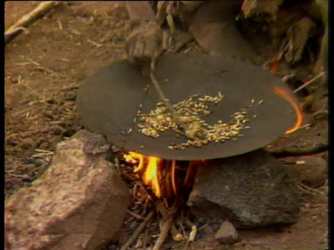 man cooking grain on pan over fire during ethiopian famine; jan 85 - hungrig stock-videos und b-roll-filmmaterial