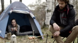 Man cooking meal near camping tent and girlfriend. Warming hotdog wide shot. Couple people in love autumn outdoor trip in nature. Fall sunny day. 4k slow motion video