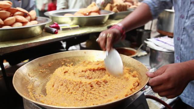 Man cooking moong dal halwa, Delhi, India
