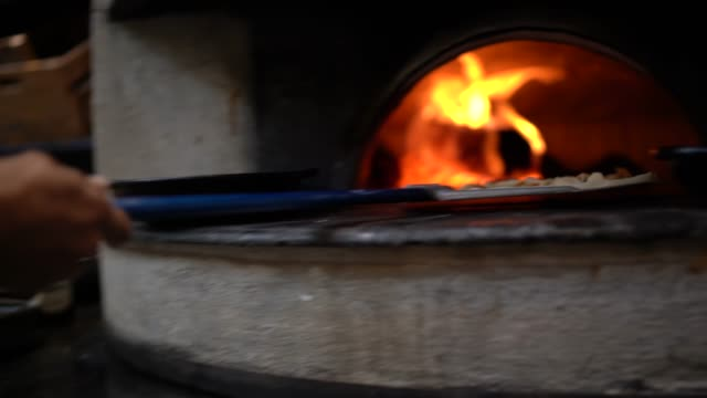 man cooking pizza in a pizza oven - pizza oven stock videos and b-roll footage