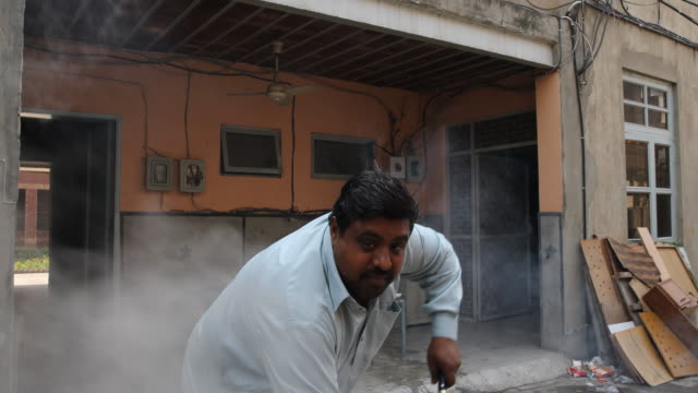 vídeos de stock, filmes e b-roll de man cooking rice on outdoor fire. - um dia na vida