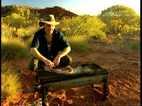 MS Man cooking steak on barbecue in outback