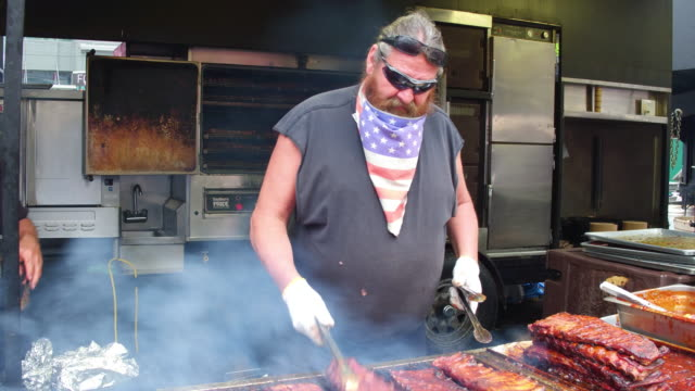 man cooking the ribs in kiosk located at one of the most important cultural intersections of the canadian city, capital of ontario province - お祭り好き点の映像素材/bロール