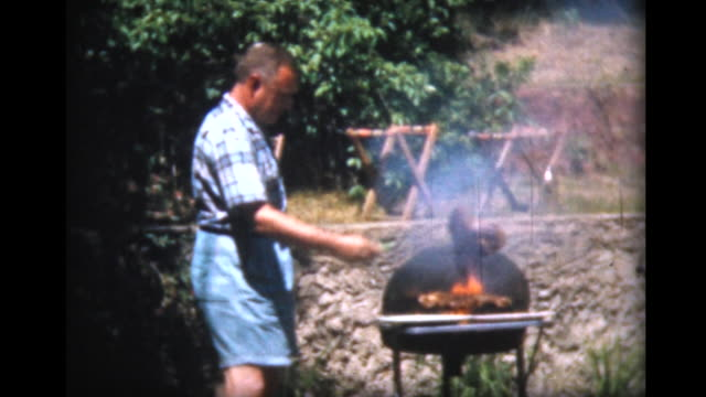 vídeos y material grabado en eventos de stock de 1957 man cooks and carves meat on open grill - 80 89 años