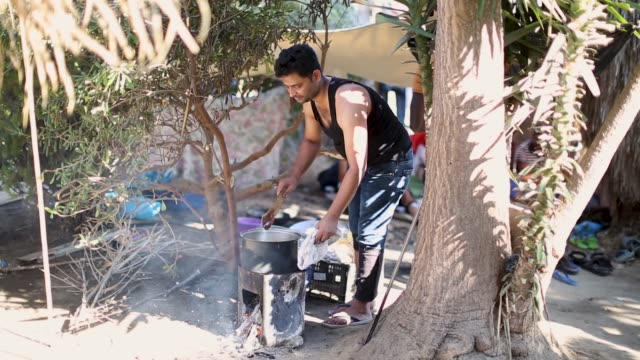 A man cooks food over a fire at an abandoned hotel that has given refuge to many migrant families on August 29 2015 in Kos Greece Migrants from many...