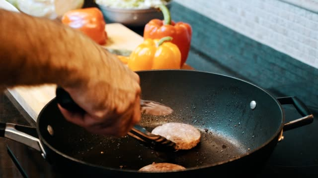 mann kocht hamburger patty in bratpfanne - orangefarbige paprika stock-videos und b-roll-filmmaterial