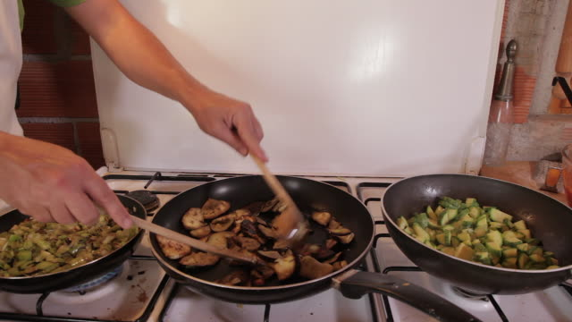 man cooks vegetables