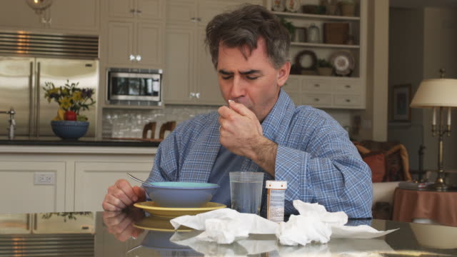 vídeos de stock, filmes e b-roll de ms man coughing and blowing nose sitting at kitchen table having bowl of soup, phoenix, arizona, usa - tossindo