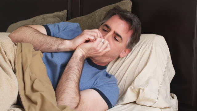 cu man coughing and shivering lying on sofa, phoenix, arizona, usa - erkältung und grippe stock-videos und b-roll-filmmaterial