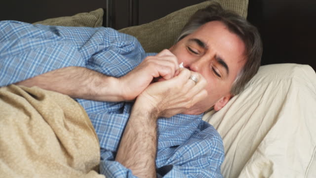 CU Man coughing and sneezing lying on sofa, Phoenix, Arizona, USA