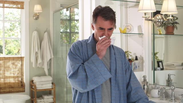 vídeos y material grabado en eventos de stock de ms man coughing and sneezing standing in bathroom, phoenix, arizona, usa - estornudar