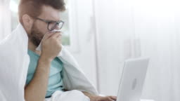 Man coughing and using laptop