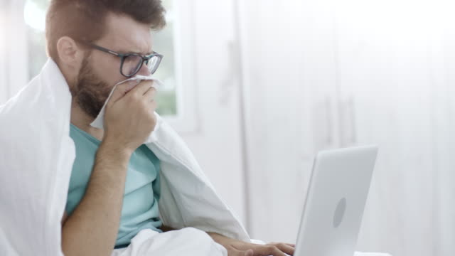 man coughing and using laptop - illness stock videos & royalty-free footage