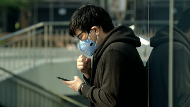 vídeos de stock e filmes b-roll de man coughing while playing phone in city with air pollution - máscara de proteção