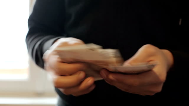 Man counting euro bills money in hands.