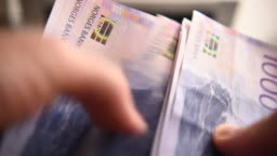 Man Counting Norwegian Krones Banknotes.