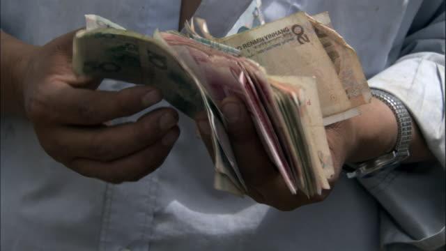 man counts money in market, kashgar, xinjiang province, china - counting stock videos & royalty-free footage