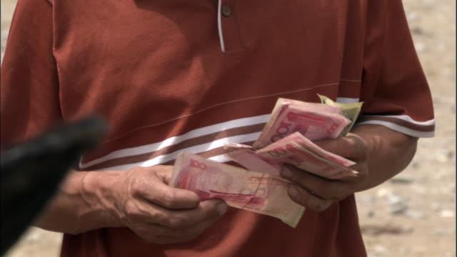 man counts money in market, kashgar, xinjiang province, china - chinese yuan note stock videos & royalty-free footage