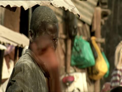 cu man covered in dust standing at kigali market / kigali, rwanda - フツ族点の映像素材/bロール