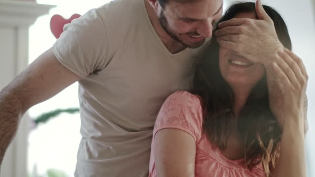 man covering his wife's eyes to surprise her with a rose and a gift - valentine's day stock videos & royalty-free footage