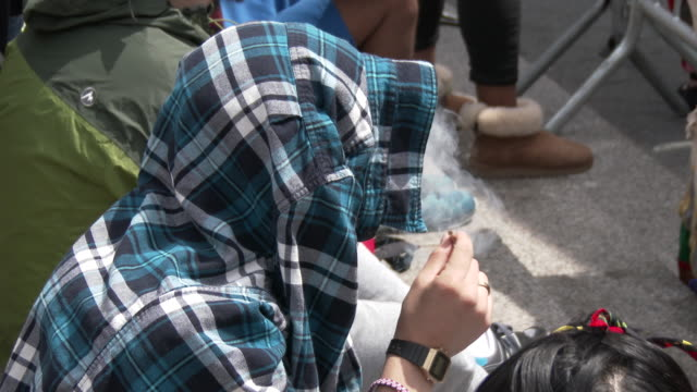 A man covers his head with a flannel shirt and smokes a joint as he listens to speakers at the annual Cannabis Day Rally in Union Square Park New York
