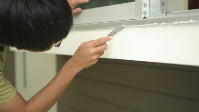 l'uomo copre la crepa nel davanzale della finestra con sigillante - sigillante video stock e b–roll