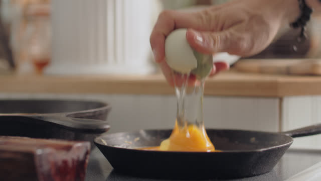 vídeos de stock, filmes e b-roll de cu man cracks egg into frying pan, saves eggshell for composting - skillet cooking pan