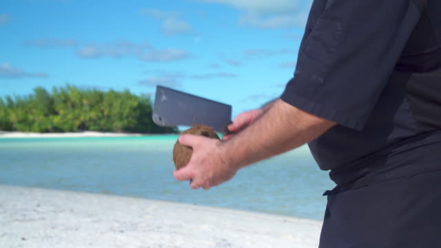 a man cracks open a coconut with a knife. - territori francesi d'oltremare video stock e b–roll