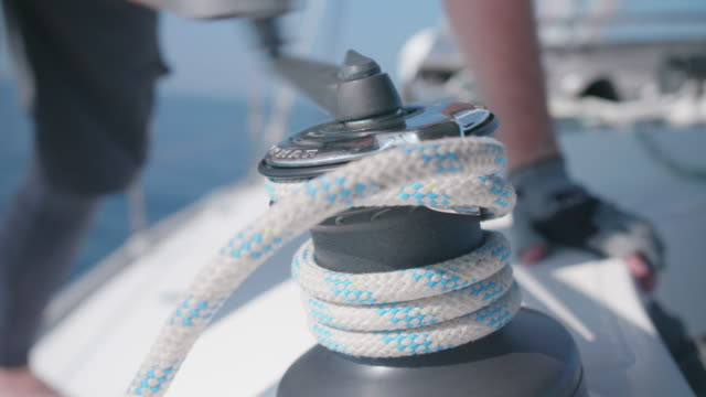 vídeos de stock, filmes e b-roll de a man cranking a winch with a handle while sailing a sailboat in the aegean sea of greece. - evitar os outros