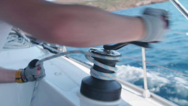 a man cranking a winch with a handle while sailing a sailboat in the aegean sea of greece. - motorboot stock-videos und b-roll-filmmaterial