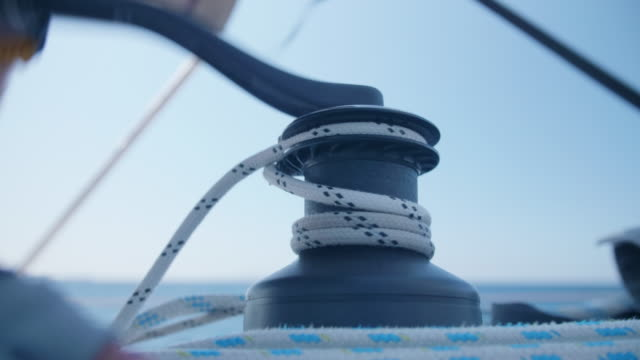 vidéos et rushes de a man cranking a winch with a handle while sailing a sailboat in the aegean sea of greece. - marin